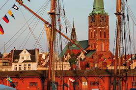 Das warme Licht der Abendsonne lässt die Seefahrerkirche St. Jakobi leuchten. Im Vordergrund sind die Masten eines Segelschiffes zu sehen, sowie die Mediadocks dahinter. - Copyright: Dr. Karen Meyer-Rebentisch