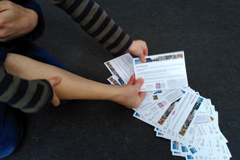 Eine Kinderhand und eine Erwachsenenhand ziehen eine Verlosungskarte aus einem am Boden liegenden Stapel