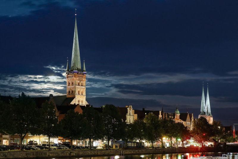 Nachtaufnahme vom St.-Petri-Turm und den beiden Dom-Türmen, beide beleuchtetet. Links vom Petri-Turm leuchtet das Mondlicht durch den wolkenbehangenen Himmel. Die Lichter der Untertrave leuchten durch die kleinen Bäume an der Promenade, die Trave ist ruhig und die Lichter spiegeln sich im Wasser.