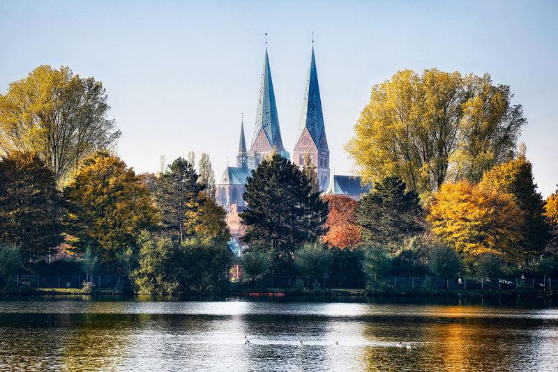 Verträumt mit einem leichten Weißschleier ragen die Türme St. Mariens in den blauen Himmel.Im Vordergrund stehen die Bäume im Herbstlaub und unter ihnen die über die Ufer getretenen Trave mit wenigen schwimmenden Enten.