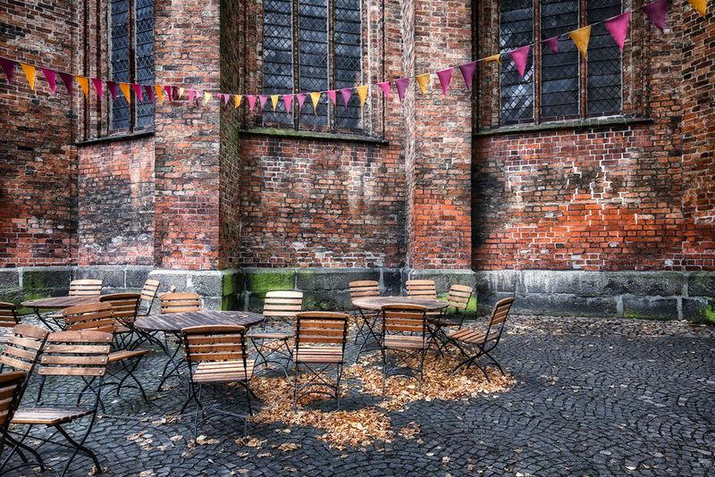 Schwarze Metall-Tische mit runder Holztischplatte, rundherum Metall-Klappstühle mit Holzsitzflächen, darüber eine bunte Gerlande, im Hintergrund die Backsteinmauern und Fenster von St. Aegidien.