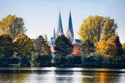 Verträumt mit einem leichten Weißschleier ragen die Türme St. Mariens in den blauen Himmel.Im Vordergrund stehen die Bäume im Herbstlaub und unter ihnen die über die Ufer getretenen Trave mit wenigen schwimmenden Enten.  - Copyright: Andreas Schwiederski