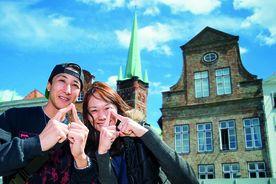 Die Japanische Touristen Jun und Kayako zeigen das Sieben-Türme-Symbol mit ihren Zeigefingern - vor dem St. Petri Turm - Copyright: Olaf Malzahn
