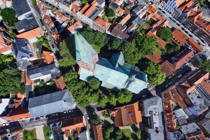 Aus der Vogelperspektive ist die St. Aegiedien-Kirche zu sehen, grüne Bäume umsäumen die Kirche - Rund um die Kirche sind die Straßen und Dächer Lübecks zu sehen.