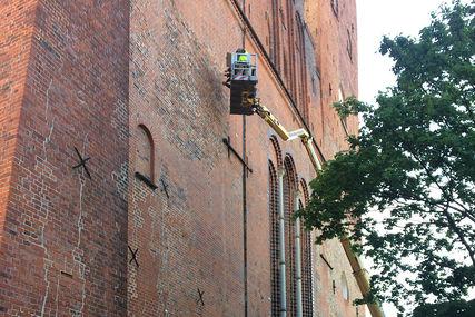 Hubsteigereinsatz - Mit ausgefahrenem Hubsteigerarm wird der Hubsteigerkorb an der Westfassade der Domtürme entlang geführt - Copyright: Ev.-Luth. Dom-Kirchengemeinde in Lübeck,