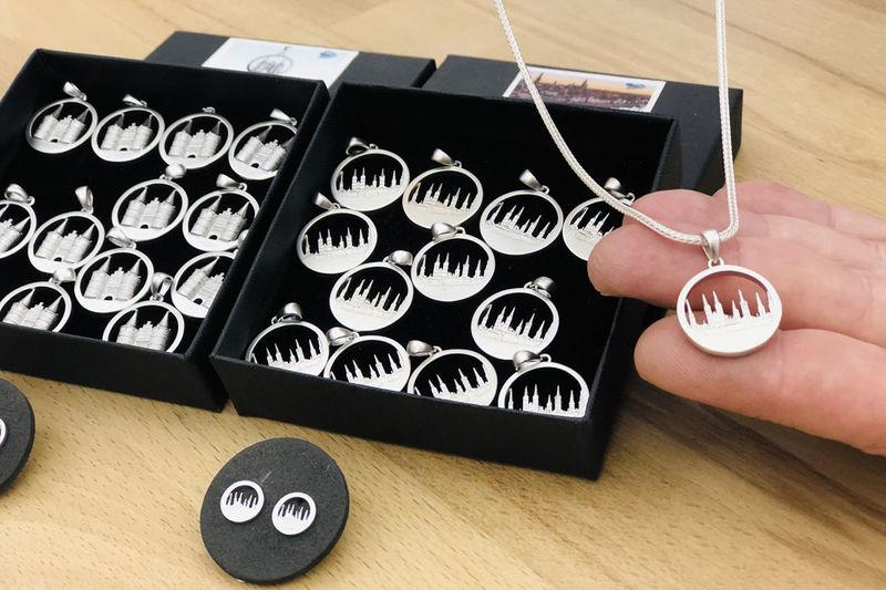 Verschiedene Anhänger liegen in zwei schwarzen Schachteln, davor ein paar Ohrringe auf dunklem Untergrund. Auf der rechten Bildhälfte sieht man die Fingerkuppen einer Hand, auf der ein Anhänger liegt. Die Kette, welche den anhänger trägt wird von der anderen Hand gehalten. Dies ist aber nicht auf dem Foto zu sehen.