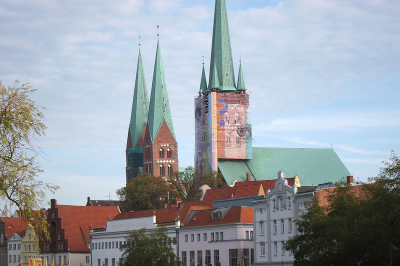 """St. Petri Lübeck - Der Turm mit Bauplane """"Auge"""" - daneben die St. Marienkirchtürme"""