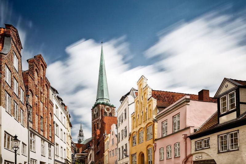 Im Hintergrund ist die St.-Jakobi-Kirche zu sehen. Im Vordergrund die Fassagen links und rechts einer Altstadtstraße Lübecks.