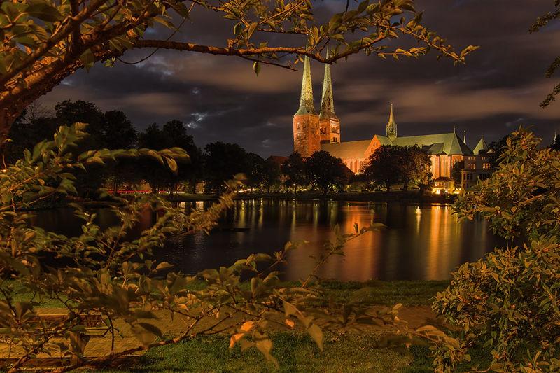 Abendstimmung am Mühlenteich. Der Dom wird beleuchtet und spiegelt sich im Mühlenteich. Die Fotografin hat das Bild zwischen Bäumen und Hecken aufgenommen, welche das Bild umrahmen.