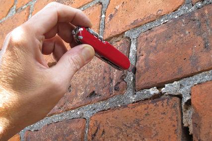 Eine Hand mit einem roten schweizer Messer, hat die Spitze des Messers in eine aufgeplatzte Fuge gesteckt. - Copyright: Ev.-Luth. Kirchenkreis Lübeck-Lauenburg