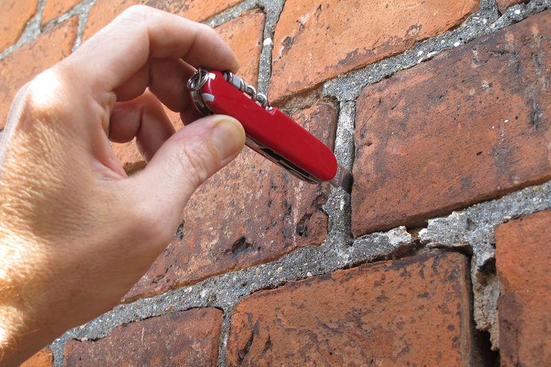 Eine Hand mit einem roten schweizer Messer, hat die Spitze des Messers in eine aufgeplatzte Fuge gesteckt.