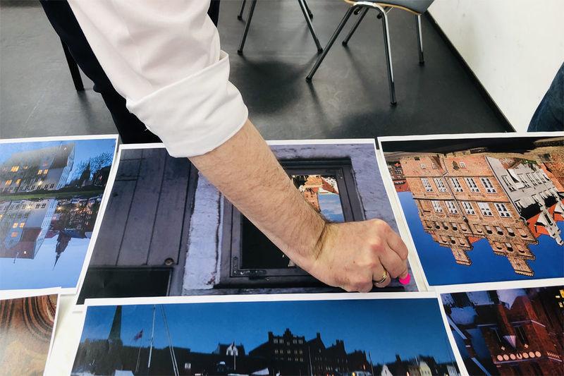 Mehrere farbige Kalenderbilder liegen nebeneinander Eine Hand klebt einen roten Klebe-Kreis auf eines der bilder