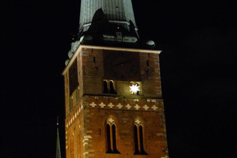 Ein leuchtender Weihnachtsstern ist unterhalb der Uhr von St. Jakobi zu sehen. Es ist Nacht.