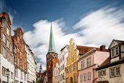 Im Hintergrund ist die St.-Jakobi-Kirche zu sehen. Im Vordergrund die Fassagen links und rechts einer Altstadtstraße Lübecks. - Copyright: Andreas Schwiederski