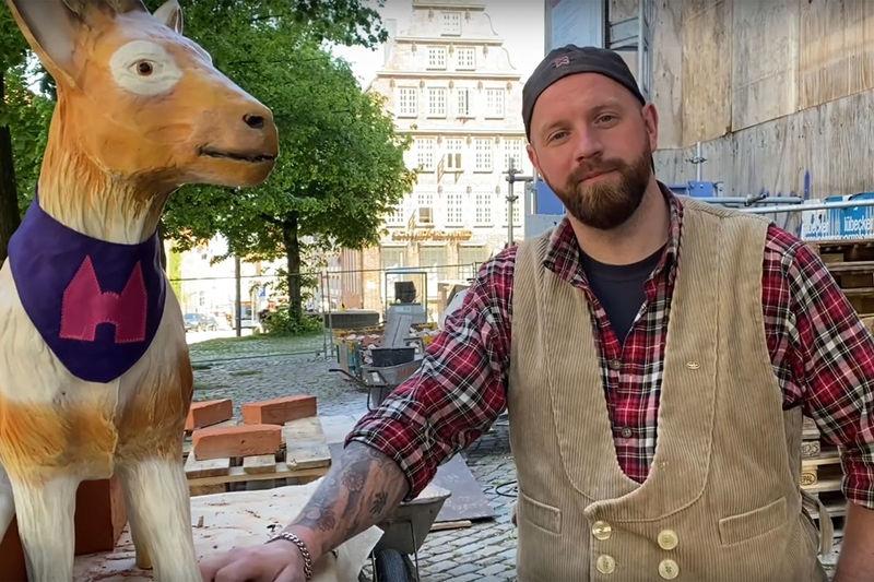 """Links steht die aus Kunstharz produzierte Ziegenfigur """"Zieglinde"""", rechts daneben steht der Hüttenmeister Marco Quandt in Arbeitskleidung. Im Hintergrund sieht man die Baustelle St. Marien."""