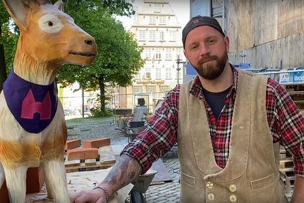 Links steht die aus Kunstharz produzierte Ziegenfigur 'Zieglinde', rechts daneben steht der Hüttenmeister Marco Quandt in Arbeitskleidung. Im Hintergrund sieht man die Baustelle St. Marien. - Copyright: Kirchenkreis Lübeck-Lauenburg