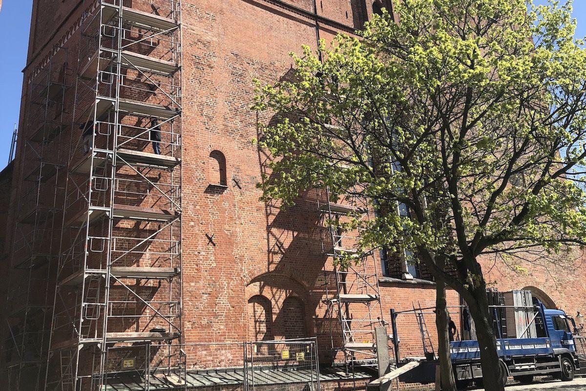 Baugerüst am Domturm auf der linken Seite, auf der rechten Seite steht ein Baum mit grünen Blättern - Copyright: Margrit Wegner