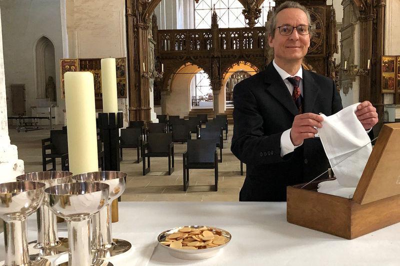 Heiko Gruhl bereitet den Altar für einen Gottesdienst mit Abendmahl vor. Zu sehen sind Oblaten und Kelche für den Wein.