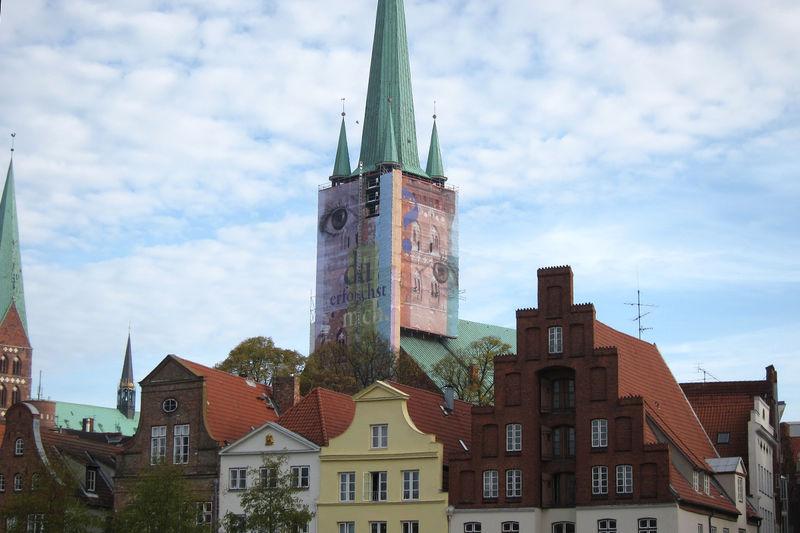 Der Turm von St. Petri Lübeck mit Bauplane über den Dächern der Obertrave