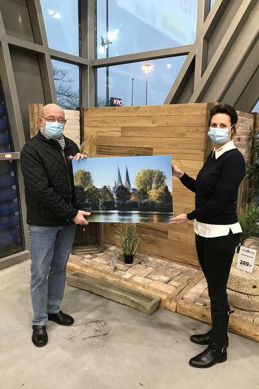 Herr Breede bekommt das Acrylbild überreicht - links Herr Breede, rechts Mitarbeiterin vom Hagebau-Markt Lübeck, zwischen Ihnen halten beide das Bild.