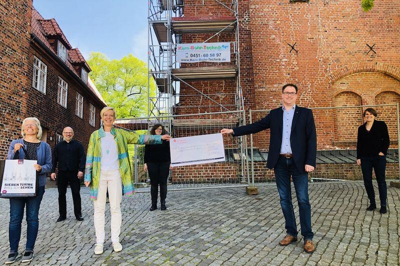 V. li.: Renate Somrau vom Verein Lübecker Stadtführer e.V., Pastor Martin Klatt, Petra Ulrich, Vikarin Carolin Sauer, Bürgermeister Jan Lindenau und Pastorin Margrit Wegner bei der Scheck-Übergabe am Dom zu Lübeck.