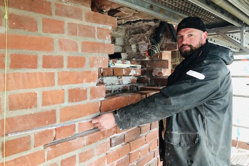 Kirchenbauhütten-Leiter Marco Quandt erklärt die Maurerarbeiten anhand des Loches, das bis zur historischen Mauer aufgestemmt wurde.