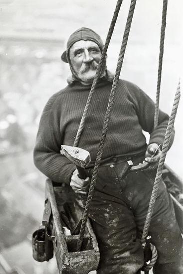 Schwarz-weiß-Fotografie: Zu sehen ist der Handwerker Paul Ruperti, welcher auf einem historischen Hochsitz sitzt und zwar direkt in schwindelnder Höhe am Turmhelm von St. Marien. Es ist eine Nahaufnahme von Ihm und er blickt direkt in die Kamera. Das Bild ist von 1922.