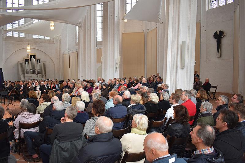 Die Abschlussveranstaltung zur St. Petri Turmsanierung war sehr gut besucht. Unter den Besuchern waren u.a. Groß- und Einzelspender, sowie Stiftungsmitglieder und Ehrenamtliche. Besucher sitzen auf Holzbänken und lauschen den Vorträgen.