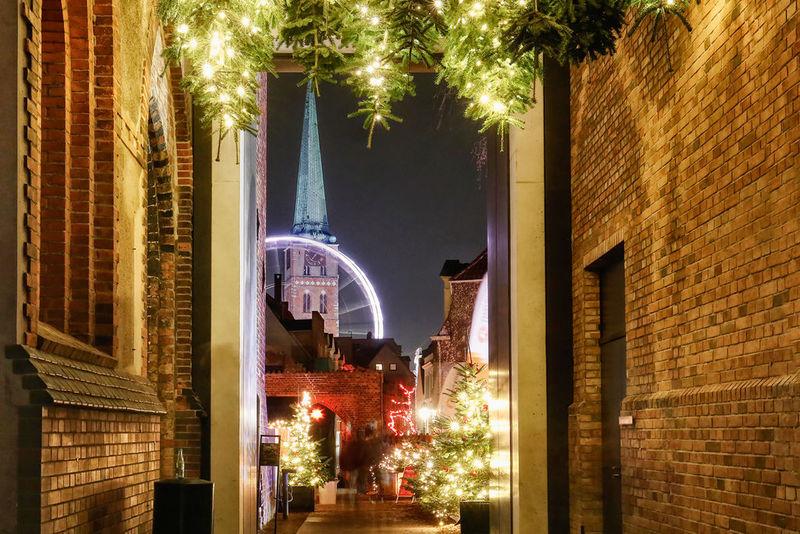 Weihnachtlich geschmückter Gang am Weihnachtsmarkt St. Jakobi. Tannen mit hellen Lichterketten ragen von oben herab. Im Hintergrund ist das fahrende Riesenrad zu sehen, dahinter Der beleuchtete Turm von St. Jakobi.