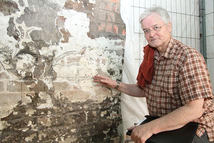 Restaurator Rinko Berg vor einer Wandmalerei. - Copyright: Ev.-Luth. Kirchenkreis Lübeck-Lauenburg