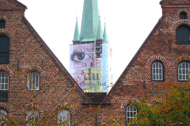 """St. Petri Lübeck mit Bauplane """"Auge"""" zwischen zwei Salzspeicher-Dachgiebeln"""