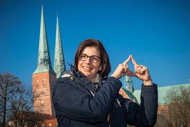 Claudia Grobecker macht das Sieben-Türme-Symbol mit ihren Zeigefingern. Die Finger zeigen eine Turmspitze. - Copyright: Ev.-Luth. Kirchenkreis Lübeck-Lauenburg