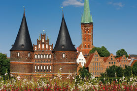 Vom Bahnhof kommend der erste Blick auf die Stadt - Im Vordergrund ist das Holstentor zu sehen, rechts daneben der Petriturm sowie die Salzspeicher - Copyright: Dr. Karen Meyer-Rebentisch