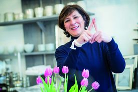 Mases Albrecht von Albrecht Deco zeigt das Sieben-Türme-Symbol mit ihren Zeigefingern. Sie steht in ihrem Geschäft, vor ihr ein Strauß rosa Tulpen - Copyright: Olaf Malzahn