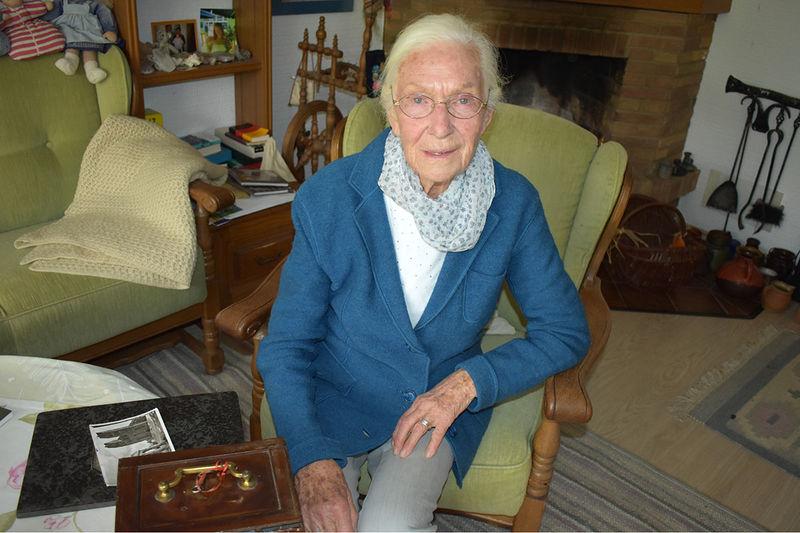 Frau Schimkat sitzt im Wohnzimmer auf einem Sessel. Vor ihr liegt ein Foto von den zerstörten Türmen St. Marien Lübeck.