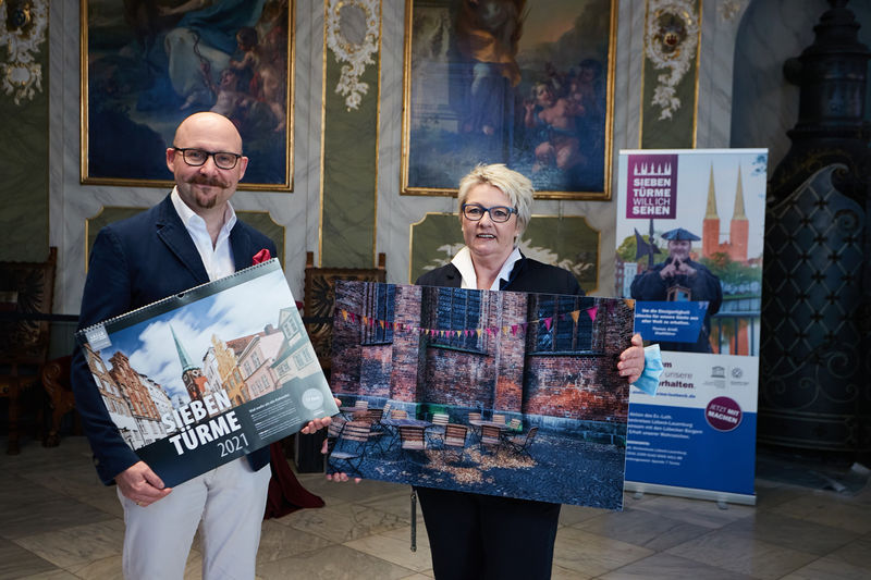 von rechts zu sehen: Olivia Kempke und Markus Endreß, beide halten ein Kalender-Acrylbild des Sieben-Türme-Kalender 2021 vor sich. Im Hintergrund ist eine Wand mit Bildern und Ornamenten des Audienzsaales Rathaus Lübeck zu sehen. Auf der rechten Seite wurde ein Roll-up aufgestellt.