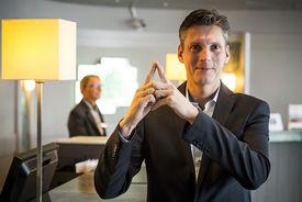 Frank Senger Generalmanager vom Holiday Inn macht das Sieben-Türme-Symbol mit seinen Zeigefingern. Die Finger zeigen eine Turmspitze. - Copyright: Olaf Malzahn