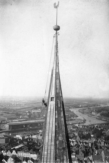 Schwarz-weiß-Fotografie: Zu sehen ist der Handwerker Paul Ruperti, welcher auf einem historischen Hochsitz sitzt und zwar direkt in schwindelnder Höhe am Turmhelm von St. Marien. Das Bild ist von 1929