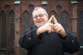 Der ehemalige Schirmherr Lienhard Böhning zeigt mit seinen beiden Zeigefingern das Sieben-Türme-Symbol - Copyright: Ev.-Luth. Kirchenkreis Lübeck-Lauenburg