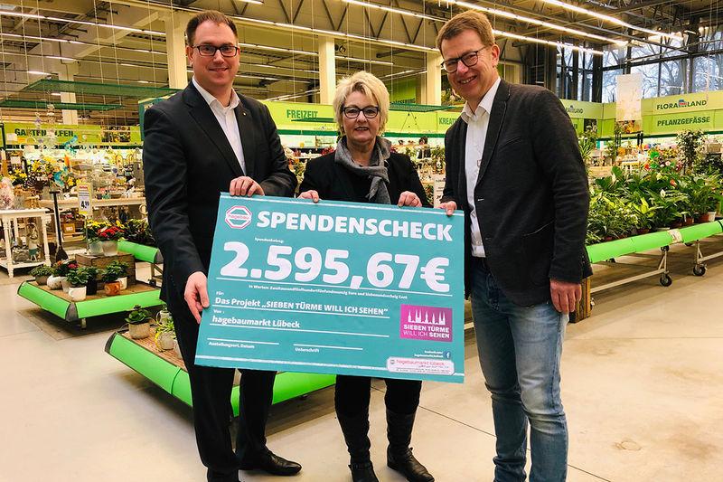 Bürgermeister Jan Lindenau, Olivia Kempke vom Lübeck Management und Hagebau-Markt-Leiter Jens-Dieter Haß stehen nebeneinander und halten einen überdimensionalen Scheck vor sich mit der Summe: 2.595,67€. Sie stehen im hagebaumarkt in der Pflanzenabteilung.