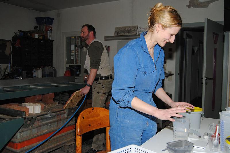 Im Vordergrund bereitet Magdalena Jakubek alles vor für die Entwicklung des Spezialmörtels. Herr Leinert ist links im Hintergrund zu sehen.