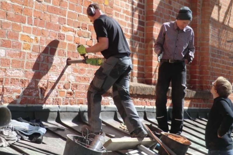 Männer bohren im Mauerwerk des Dom zu Lübeck.