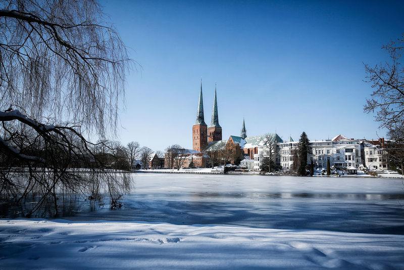 Im Vordergrund der leicht überfrorene Mühlenteich umrandet von Bäumen ohne Blätter. Im Hintergrund der Dom zu Lübeck. Die Türme ragen in den wolkenlosen, blauen Himmel