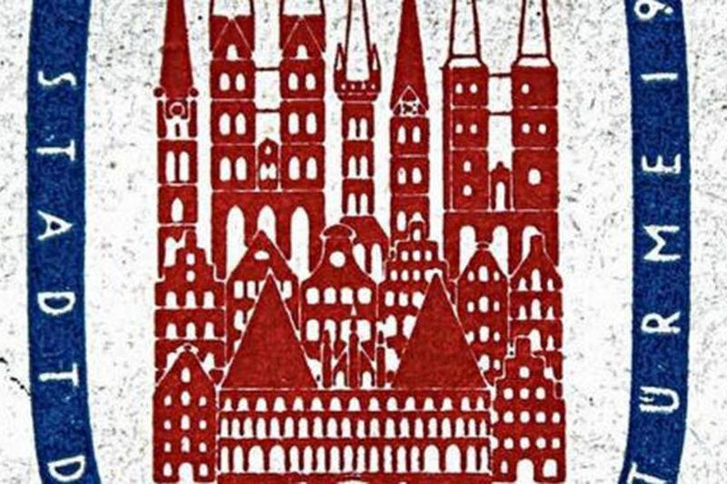 Man sieht den Ausschnitt der Briefmarke von 1956. In der Mitte sieht man in roter Farbe Dächer von Lübeck, sowie die Kirchen und das Holstentor. Umrandet sind diese Häuser von einem blauen breiten Ring, auf dem in weißer Schrift: Stadt und Türme aufgedruckt sind