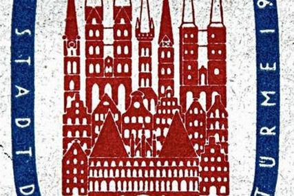 Man sieht den Ausschnitt der Briefmarke von 1956. In der Mitte sieht man in roter Farbe Dächer von Lübeck, sowie die Kirchen und das Holstentor. Umrandet sind diese Häuser von einem blauen breiten Ring, auf dem in weißer Schrift: Stadt und Türme aufgedruckt sind - Copyright: Stadtarchiv Hansestadt Lübeck