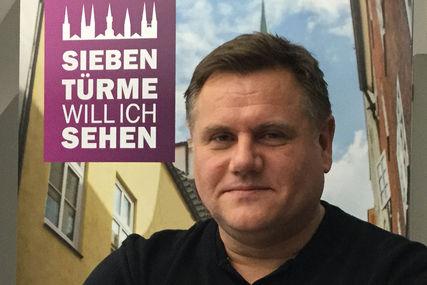 Portraibild Fundraiser Christian Hohmann - links neben ihm ist das Logo 'Sieben Türme will ich sehen' platziert.  - Copyright: Ev. Luth. Kirchenkreis Lübeck-Lauenburg