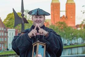 Stadtführer Thomas Arndt steht vor dem Dom. Zischen ihm und dem Dom sieht man die Untertrave. Er ist im Nachtwächter-Outfit, hält eine kleine Öllaterne in der linken Hand und zeigt mit den Zeigefingern das Turmsysmbol. - Copyright: Christine Rudolf