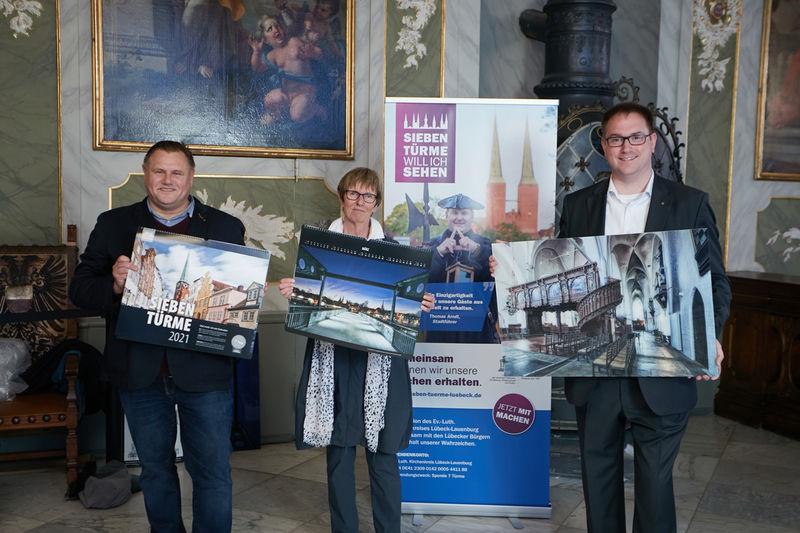 v.l.Christian Hohmann, Cornelia Schäfer und Schirmherr Bürgermeister Jan Lindenau halten jeweils ein Sieben-Türme-Kalender-Acrylbild vor sich. Im Hintergrund ist ein Roll-up zu sehen sowie die bebilderte Wand des Audienzsaals Rathaus Lübeck.