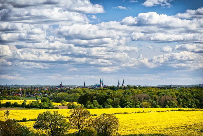 Silhouette Lübecks im Hintergrund, der Himmel ist wolkenverhangen, im Vordergrund sind gelbe Rapsfelder zu sehen und grüne Bäume.