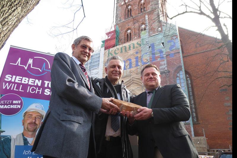 Dr. Bernd Schwarze (links im Bild) hält gemeinsam mit Theo Dräger (mitte) und Fundraiser Christian Hohmann (rechts) einen Rippenstein. Im Hintergrund ist links das Logo von den Sieben-Türmen auf einem Roll-up zu sehen. Auf der rechten Seite im Hintergrund ist St. Petri zu sehen.